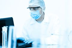 Scientist working in the lab. In protective mask and cap, examines a test tube with liquid Royalty Free Stock Image
