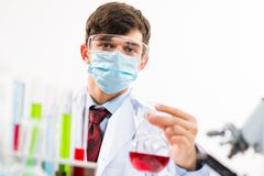 Scientist working in the lab. In protective mask, examines a test tube with liquid Royalty Free Stock Photo