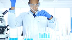 Scientist Working in Laboratory, Pouring Chemical Solution in Test Tube. 4k , high quality Stock Image