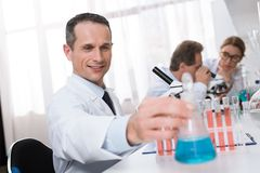 Scientist working in laboratory. Smiling male scientist in white coat holding flask with blue reagent in chemical lab Royalty Free Stock Photography