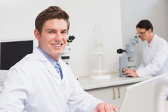Scientist working with laptop and another with microscope Stock Photos