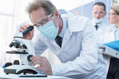 Scientist working with microscope. Focused male scientist in white coat and protective gear, working with microscope in chemical lab Stock Photo