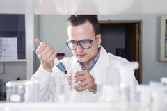 Scientist works in laboratory. Caucasian male chemist scientific researcher working with pipettes in chemical or medical laboratory Royalty Free Stock Image