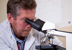 Scientist works with microscope. Scientist in white coat works with microscope Royalty Free Stock Photo