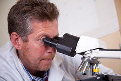 Scientist works with microscope. Scientist in white coat works with microscope Royalty Free Stock Images