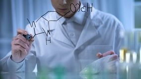 Scientist writes formula planning to invent new fertilizer, theoretical research stock photography