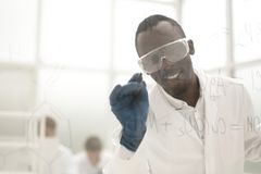 Scientist writing chemical formula on a glass Board stock photography