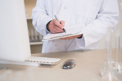 Scientist writing on clipboard. In the laboratory Stock Images
