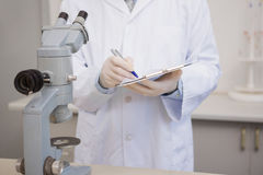 Scientist writing on clipboard. In the laboratory Stock Photography