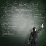 Scientist writing formulas on chalkboard. Young man in suit drawing chemistry formulas on chalkboard Royalty Free Stock Image