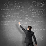 Scientist writing formulas on chalkboard. Young man in suit drawing chemistry formulas on chalkboard Stock Images