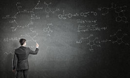 Scientist writing formulas on chalkboard. Young man in suit drawing chemistry formulas on chalkboard Royalty Free Stock Photography