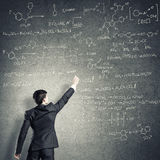 Scientist writing formulas on chalkboard. Young man in suit drawing chemistry formulas on chalkboard Stock Photos
