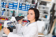 Scientist young woman using a microscope Stock Photo
