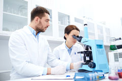 Scientists with clipboard and microscope in lab Stock Image