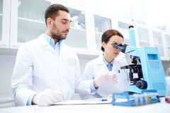 Scientists with clipboard and microscope in lab Stock Photos