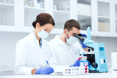Scientists with clipboard and microscope in lab Royalty Free Stock Photography