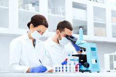 Scientists with clipboard and microscope in lab. Science, chemistry, technology, biology and people concept - young scientists with test tube and microscope Royalty Free Stock Images