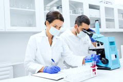 Scientists with clipboard and microscope in lab Stock Images
