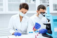 Scientists with clipboard and microscope in lab Stock Photo