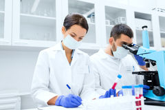 Scientists with clipboard and microscope in lab Stock Photography