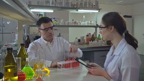 Scientists conducting research. Adult doctor or lab technician holding glass bulb with liquid. Discussing and analyzing their findings with assistant caucasian stock video footage