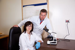 Scientists coworkers near by microscope Royalty Free Stock Photos