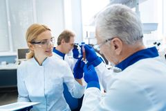 Scientists discussing analysis process in the lab. Developing medicine. Grey-haired bearded old scientist holding a test tube and looking at it and a smiling Stock Photo