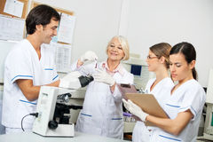 Scientists Discussing Over Blood Sample In. Team of scientists discussing over blood sample in medical laboratory Royalty Free Stock Photos