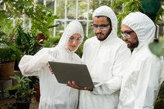 Scientists discussing over laptop at greenhouse. Scientists in clean suit discussing over laptop at greenhouse Royalty Free Stock Photography