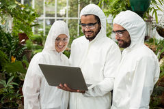 Scientists discussing over laptop. Scientists wearing clean suit discussing over laptop at greenhouse Stock Photos