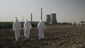 Scientists dressed in hazmat suits carefully walking across a contaminated field near a power plant -. Scientists dressed in hazmat suits carefully walking stock footage