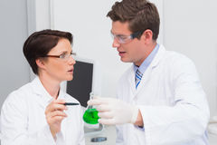 Scientists examining attentively beaker with green fluid Stock Image