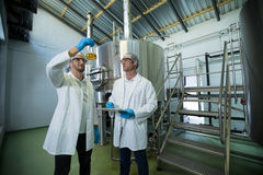 Scientists examining beer in beaker. At factory Stock Image