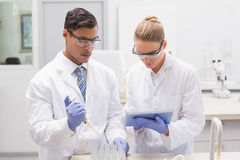 Scientists examining tubes in tray using tablet pc Royalty Free Stock Image