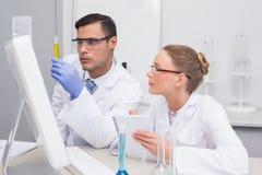Scientists examining yellow precipitate in tube Royalty Free Stock Photos