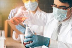 Scientists are experimenting with chemicals in science tubes at royalty free stock photo