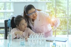 Scientists are explaining the experiment. The doctor is teaching girls to experiment in the lab. Girl studying science. royalty free stock images