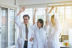 Scientists hands rais up,Group of diversity people teamwork in laboratory,Success and reserch working stock photo