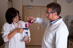 Scientists holding labware. Performing filtration test Royalty Free Stock Image