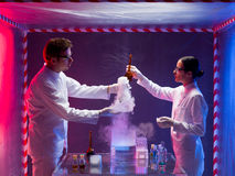 Scientists inside a biohazard space testing toxic. Photograph of a male and female scientists inside a biohazard protective space testing the toxic chemicals Stock Images