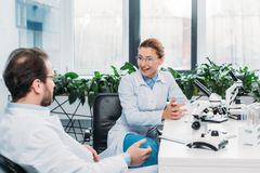 Scientists in lab coats and eyeglasses discussing work at workplace. In lab stock photos