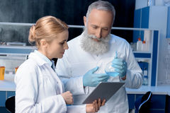 Scientists in lab coats looking at digital tablet in laboratory. Pensive scientists in lab coats looking at digital tablet in laboratory royalty free stock photo