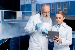 Scientists in lab coats looking at digital tablet in laboratory. Thoughtful scientists in lab coats looking at digital tablet in laboratory stock photography