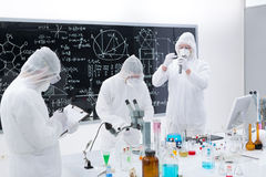 Scientists laboratory analysis. General-view of three scientists in a chemistry lab  manipulating lab tools, testing and using chemical techniques around a lab Royalty Free Stock Images