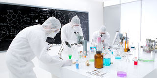 Scientists laboratory experiment. General-view of three people working in a chemistry lab with colorful liquids and transparent tools on a lab table with a Royalty Free Stock Photos