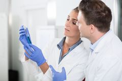 Scientists in laboratory looking at blue liquid in vial Royalty Free Stock Photo
