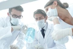 Medical researcher microbiology experiment in the laboratory. Scientists in the laboratory wearing protective goggles, looking at the flask Stock Images