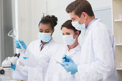 Scientists looking at beaker and taking notes Stock Photography