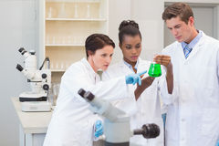 Scientists looking at green precipitate Royalty Free Stock Photography